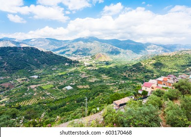 travel to Italy - above view of green gardens and Francavilla di Sicilia town in mountain valley from Castiglione di Sicilia town in Sicily