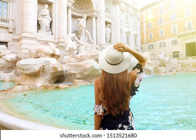 Travel in Italy. Back view attractive young woman looks Trevi fountain famous landmark in Rome. Happy girl enjoy Italian holiday in Europe.