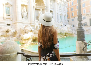 Travel in Italy. Back view of attractive woman looks Trevi fountain famous landmark in Rome. Happy girl enjoy Italian holiday in Europe.