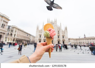 Travel, Italy, gelato and holidays concept - Ice cream in front of Milan Cathedral Duomo