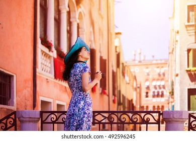 Travel to Italy. Young woman traveler in summer dress and blue hat with camera posing on the bridge in Venice. Venice is popular tourist place in Europe. Lady travel to Venice.