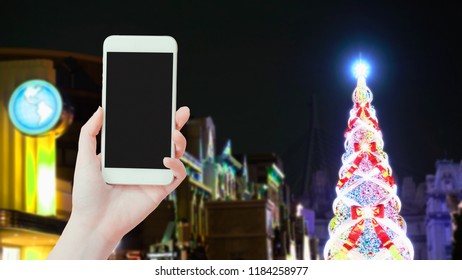 travel japan and technology concept from beauty hand hold smart phone support travel with low light old town (hogwarts) and with beautiful decorate christmas tree background