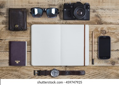 Travel journal surrounded by travelling related items including passport wallet sunglasses camera smartphone and watch
