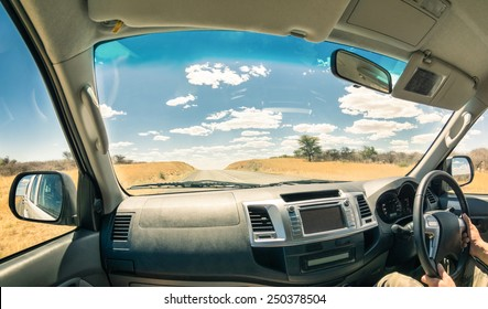 Travel journey from a car cockpit - Concept of adventure trip on the road to namibian exclusive destinations - Fisheye view on desert freeway in Namibia - Soft focus on landscape and clouds