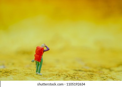 Travel and Journey concept. Woman traveler miniature figure with backpack standing on world map.