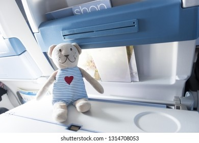 Travel with kids by plane concept, with a teddy bear on the table on board of aircraft