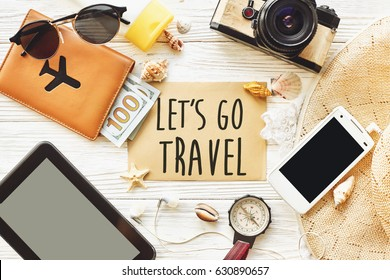 travel. let's go travel text sign concept on card flat lay, camera sunglasses compass passport money phone hat shells on white wooden background top view. wanderlust and adventure