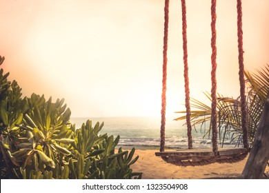 Travel lifestyle beach swing sea sunset palm trees sunlight island background vintage style copy space