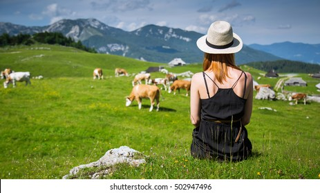 Travel, Lifestyle Concept. Beautiful woman enjoys views of the alpine village in the mountains. Velika Planina or Big Pasture Plateau in the Kamnik Alps, Slovenia.