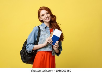 Travel and Lifestyle concept: Full length studio portrait of pretty young student woman holding passport with tickets. Isolated on bright yellow background.