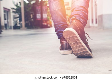 Travel Lifestyle vacations concept .walk in urban city.Close up view on man's legs in jeans and brown leather boots with sunlight against tower building blur background. Selective focus vintage tone