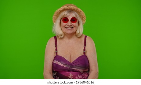 Travel, long awaited summer holiday vacation, beach party. Senior old woman tourist in swimsuit bra and red sunglasses, looking at camera, smiling on chroma key. Grandmother relaxing on sea resort