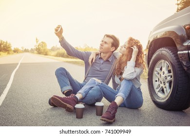 Travel. Lovely couple making a selfie, sitting on the road with coffee
