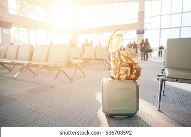 travel luggage with passenger blur background in airport terminal with vintage tone and flare filtered