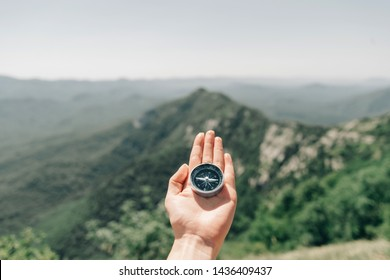 Travel magnetic compass on palm female hand on background of mountain ridge in summer outdoor, point of view.