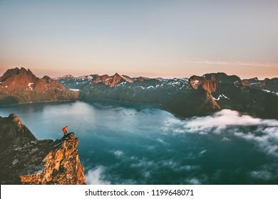 Travel man alone on the edge cliff in mountains above fjord hiking adventure lifestyle extreme vacations sunset landscape in Norway