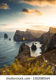 Travel man alone on the edge cliff se díva na oceán, hiking adventure lifestyle extreme vacations sunset landscape in Portugal, Madeira