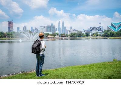 Travel man or backpacker stand enjoying with beautiful landscape of Kuala Lumpur skyscraper at Titiwangsa park Kualalumpur city, Malaysia.