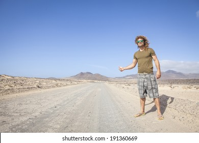 Travel man hitchhiking. attractive young man hitchhiker by the road during trip in the desert