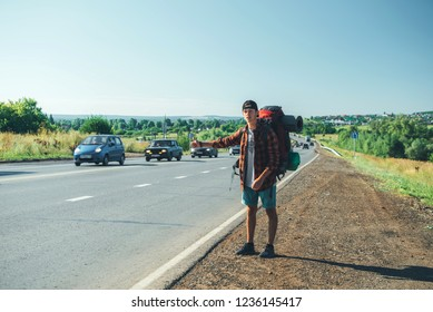 Travel man hitchhiking. Backpacker on road.