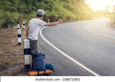 Travel man hitchhiking. A hitchhiker by the road during vacation trip in mountains at sunset. The concept of traveling and hitchhiking.