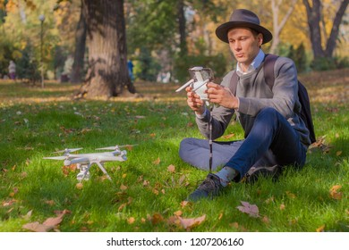 Travel man holding drone quad copter and remote control on green field