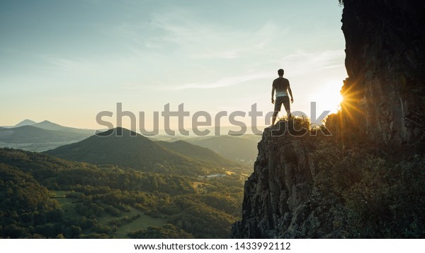 Travel man tourist alone on the edge cliff mountains and looking on the valley. Silhouette of the person on the high rock at sunset. Hiking adventure lifestyle extreme vacations.