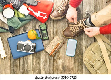 Travel man tying boots for trekking day top view of items for hiking and adventure - Active male hands on shoelaces above angle with camera mobile phone and backpack on old wooden floor background