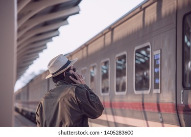 Travel man wait train at platform - people vacation lifestyle activities at train station transportation concept