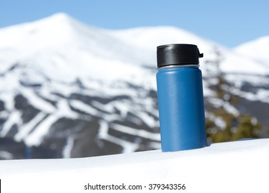 Travel Mug In The Mountains - This is an image of a blue travel coffee mug sitting in a snow bank with a big mountain in the background. Shot with a shallow depth of field.