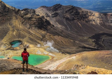 Travel New Zealand, Tongariro National Park. Young tourist hiker man overlooking volcanic landscape of Tongariro Alpine Crossing. Popular tourist trail / day hiking track in North Island