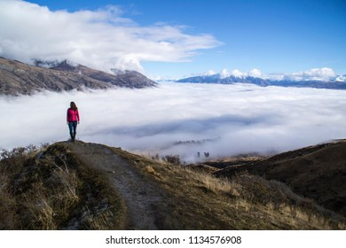 Travel New Zealand. Young touris hiker woman enjoying mountain landscape winter view and misty foggy valley over Queenstown, South Island