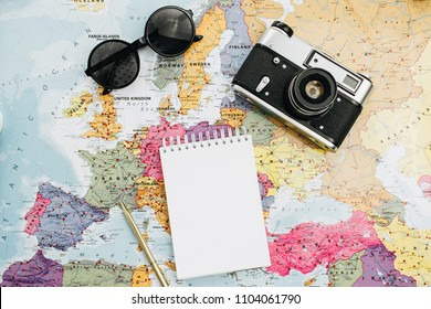 Travel notes mock up. World map, camera, sunglasses and notebook. Flat lay, top view.