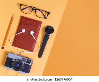 travel objects and accessories on orange background with passport camera and plane