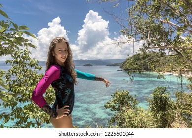 Travel on the Philippine islands, summer holidays, travel, people and vacation concept - happy young woman pointing finger on tropical beach on the island.
