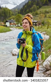 Travel and outdoor activities concept. Optimistic lovely female hiker walks by small mountain stream, holds professional photocamera, makes photos of landscape, green forest and small house behind