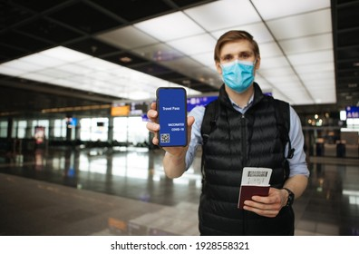 Travel Pass. Hand holding mobile Digital vaccine passport COVID-19 app. Man wearing face mask. Covid pass for traveling.  Phone in airport terminal in background. Vaccinated person ready for trip