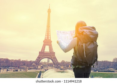 travel and people concept ,Back of travel woman in Paris ,France, with Eiffel Tower looking a map and city guide over eifel and vintage sky background in the morning