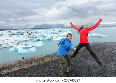 Travel people having fun jumping on Iceland excited by Jokulsarlon glacial lagoon / glacier lake. Happy funny tourists enjoying beautiful Icelandic nature landscape with Vatnajokull in background.