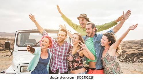 Travel people having fun taking selfie with smartphone camera in desert at sunset  - Group of happy doing excursion with convertible 4x4 car - Friendship and vacation concept - Focus on left guys