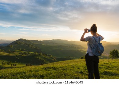 Travel, photo and real life concept - woman taking photo on mobile phone at the mountain peak