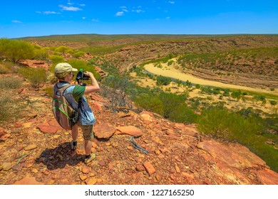 Travel photographer backpacker with stabilizer takes shot at Murchison River Gorge in Kalbarri National Park, Western Australia. Videomaker with professional camera takes photo in Australian outback.
