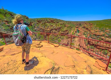 Travel photographer backpacker with stabilizer takes shot at Z-Bend lookout in Kalbarri National Park, Western Australia. Videomaker with professional camera takes photo in Australian outback.