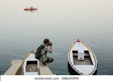 Travel photographer doing pictures seating near river with wooden boat