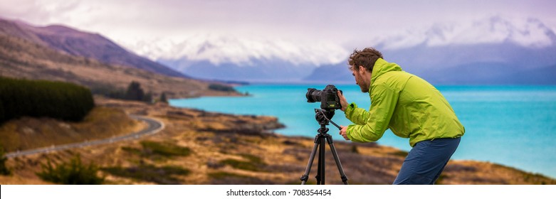 Travel photographer man taking nature video of mountain landscape at Peter's lookout, New Zealand Banner. Hiker tourist professional videographer on adventure vacation shooting slr camera on tripod.