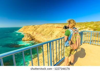 Travel photographer with stabilizer takes shot of Natural Bridge lookout in Kalbarri National Park, WA, Australian Outback. Videomaker with professional camera takes photo of Indian Ocean cliffs.