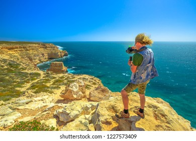 Travel photographer with stabilizer takes shot of Island Rock in Kalbarri National Park, Western Australia, in a sunny day with blue sky. Professional videomaker takes photo of Australian Coral Coast.