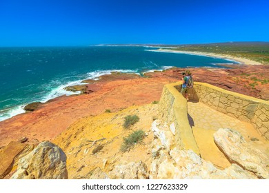 Travel photographer with stabilizer takes shot at Red Bluff lookout, Kalbarri National Park, Western Australia. Professional videomaker takes photo of Australian Coral Coast on Indian Ocean.Copy space