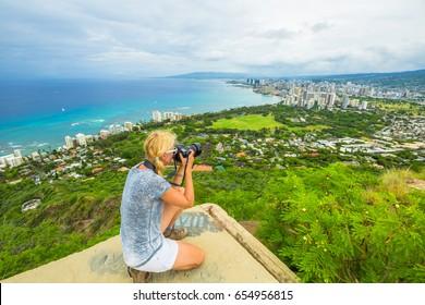 Travel photographer takes a shot of Honolulu and Waikiki beach, Oahu in Hawaii from Diamond Head State Monument. Nature photographer taking pictures outdoors during hawaiian hiking Diamond Head hike.