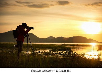 Travel photographer taking a photo with nature the lake in sunset to nightlife with camera on tripod, Focusing attention nature mountain view and lake,  Natural photography relaxing concept.